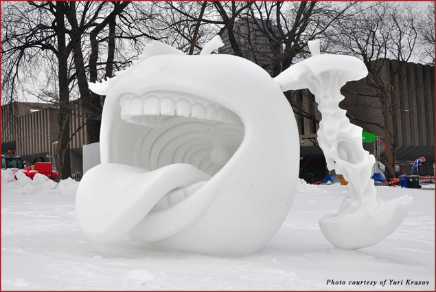 A creative snow sculpture depicting an apple with a human mouth, and an apple core, apparently right after being cannibalized