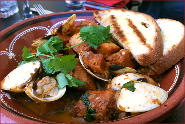 Pieces of pork and clams in the shell were cooked in a flavourful sauce, sprinkled with verdant cilantro and served with grilled bread