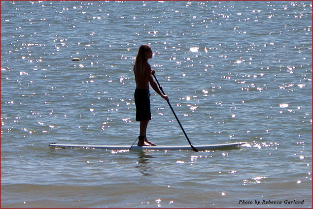 In between watersports customers, Miguel paddleboards along Playa La Ropa