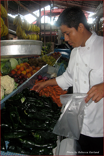 The Tides' chef, Mario, selects vegetables from the locals' market in preparation for a cooking class