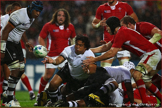 Campese Ma'afu of Fiji passes the ball clear of Welsh players