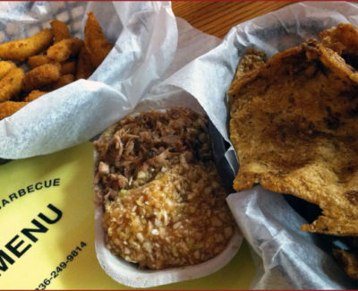 Chopped 'cue and slaw flanked by hush puppies and pork skins
