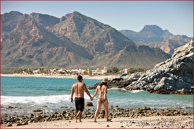 A couple strolls on the beach in San Carlos