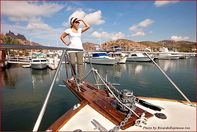 A woman poses on the prow of a boat in the marina at San Carlos, Sonora, Mexico