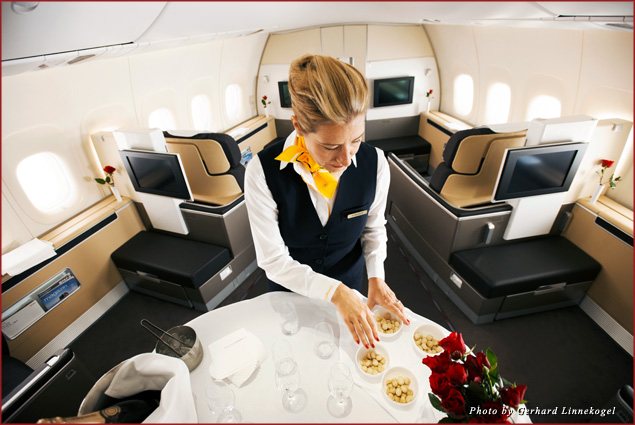 A flight attendant prepares the bar in first class