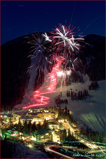 Skiers hold torches as they glide down the mountain in Taos Ski Valley, creating a trail of light