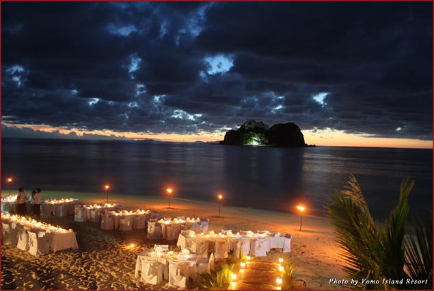 Torch-lit tables on the sand await New Year's Eve revelers in Vomo Island, Fiji