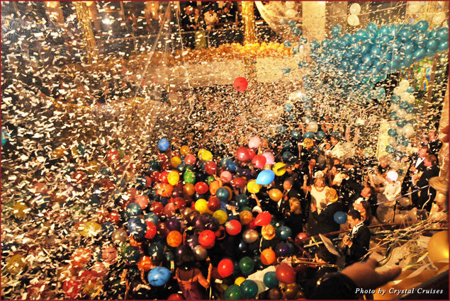 Balloons and confetti decorate partygoers at midnight during a Crystal Cruises New Year's Eve soiree