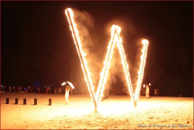 "Fire dancers set a giant ""W"" aflame during a New Year's Eve party at the W Resort in the Maldives"