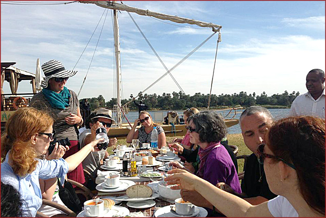 Members of a cruise enjoy a meal on the banks of Egypt's Nile River