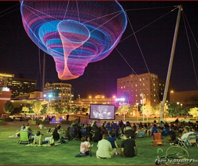 "Downtowners on the grass of Civic Space Park in Phoenix for a free screening of the film Casablanca, seated underneath Janet Echelman's art installation ""Her Secret is Patience"""