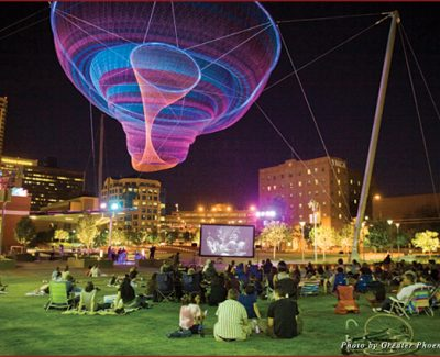 """Downtowners on the grass of Civic Space Park in Phoenix for a free screening of the film Casablanca, seated underneath Janet Echelman's art installation """"Her Secret is Patience"""""""