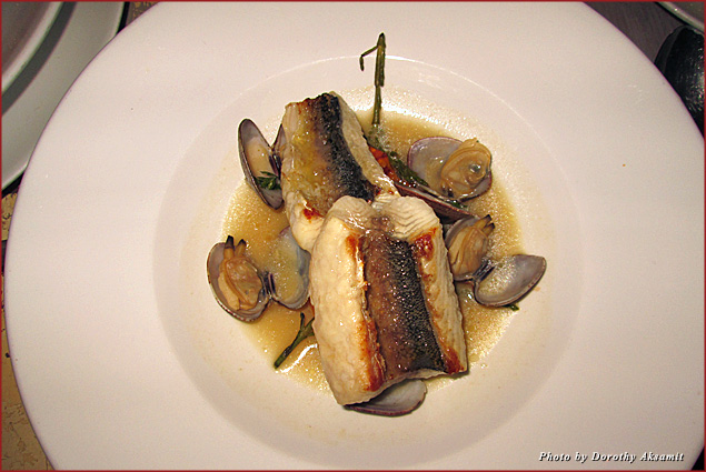 Grilled red snapper swimming in a broth with four clams