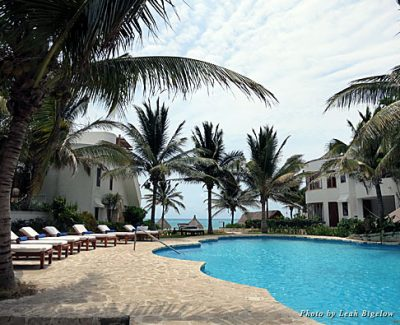 The palm tree-lined pool and surrounding guestrooms seem to blend into the beach at Maroma Resort & Spa