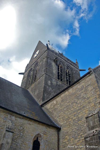 A replica of Private John Steele dangles from the church steeple in Sainte-Mère-Eglise