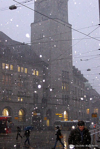 Snow falling during rush hour outside the train station in St. Gallen