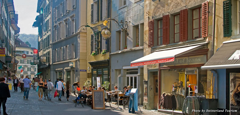 Historical buildings clad in frescos border picturesque squares in Lucerne's Old Town