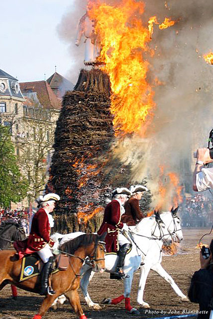 Guild members on horseback ride large circles around the flaming effigy as music plays and thousands roar