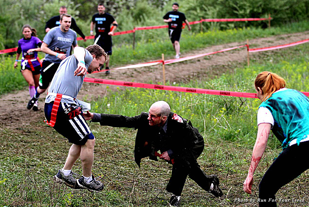 A zombie reaches for a runner's flag during the Zombie Run