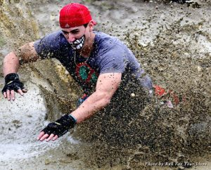 A Zombie Run participant splashes through the mud