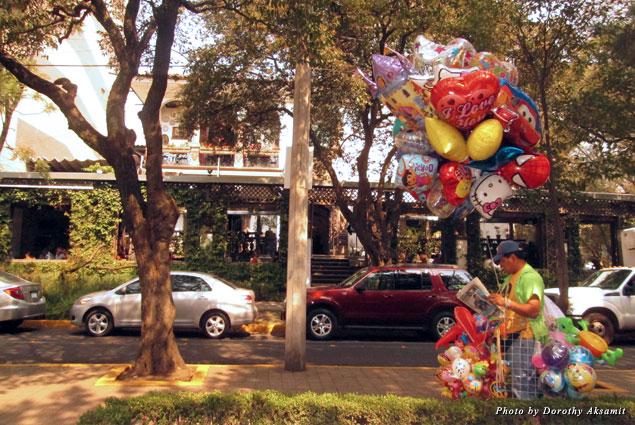A laid-back balloon vendor waits for a sale in Polanco