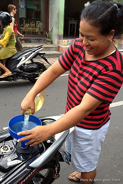 A Balinese woman gets the scooter ready to take out on the road