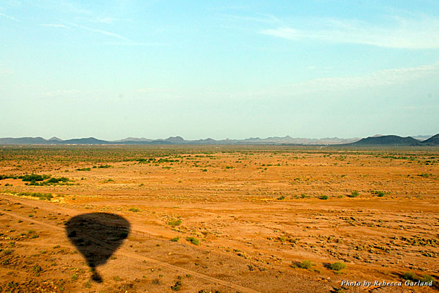 Shadow of the hot air balloon over the desert