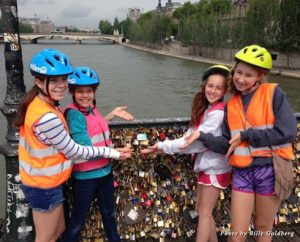 "The girls pose in front of Paris' ""love lock"" bridge during our bike tour"