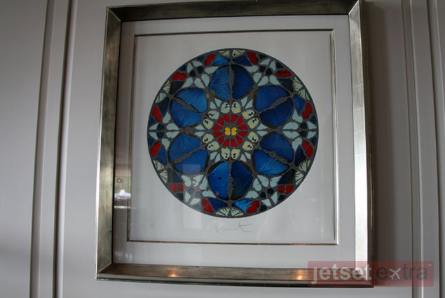 """The Damien Hirst diamond-dusted silk screen """"Psalm print: Verba mea auribu,"""" located to the left of the front desk"""