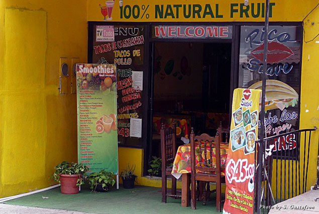 "The bright yellow entrance and the ""100% Natural Fruit"" sign beckon you to come inside and have a refreshing and delicious fruit smoothie"