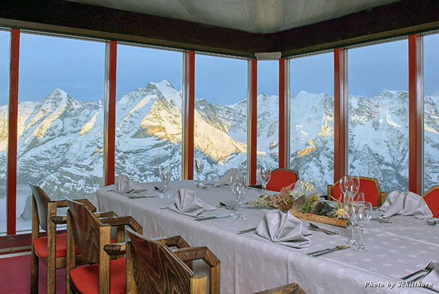 A dining table set up at Piz Gloria, with a view of the Alps in the distance