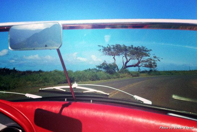 Driving along Hana Highway in a Porsche speedster