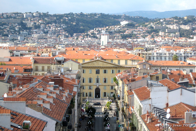 A view of Nice's red-tiled roofs and green mountains