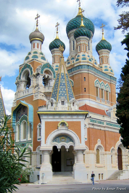 The Russian Orthodox cathedral features a teal, corral, and gold exterior