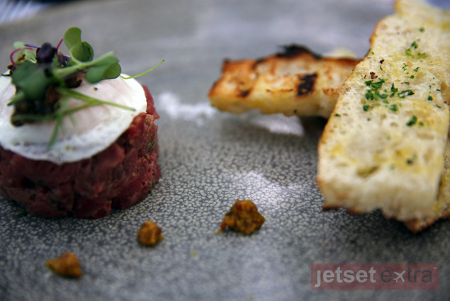 Tartar of beef tenderloin with house-grain mustard, fried egg, capers, and griddled focaccia