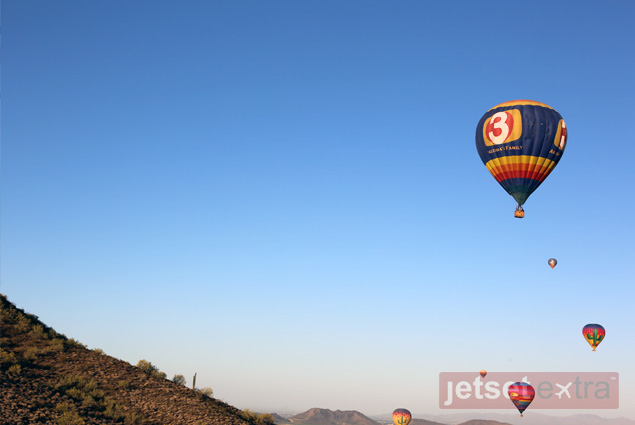 Hot air balloons fly high over the mountains outside Scottsdale