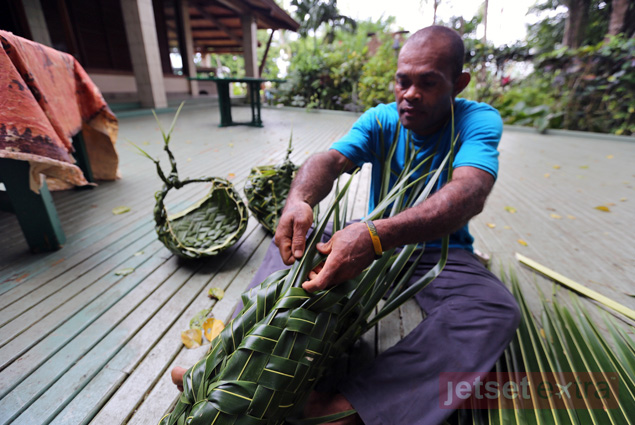 At Koro Sun Resort a man demonstrates how to use palm fronds to weave a fisherman's basket lage