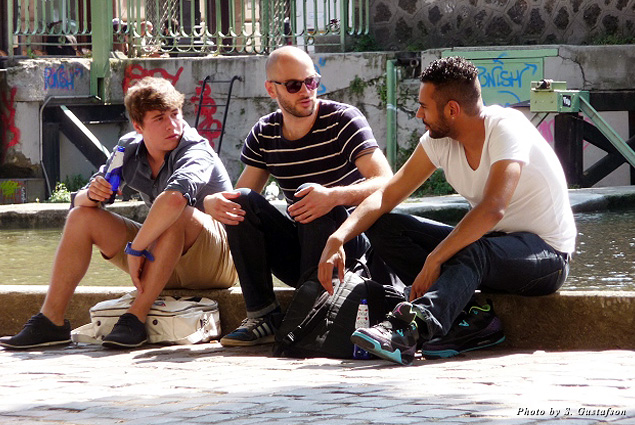 Three friends gather along Canal St. Martin to chat and discuss their weekend plans