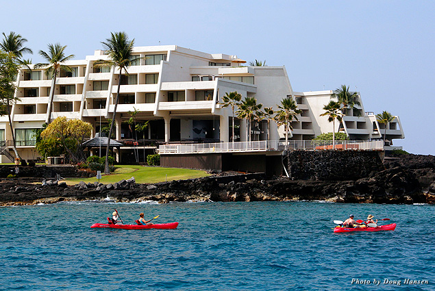 Kayakers pass by the Sheraton Kona hotel perched on a lava shelf by the ocean
