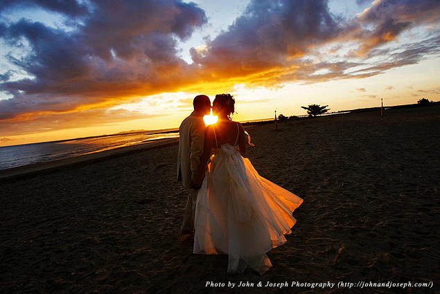 A newlywed couple walk on the beach at sunset