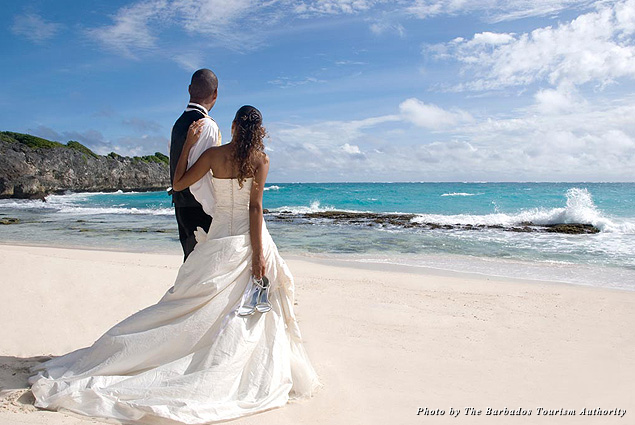 A bride and groom walk barefoot in the sand during their Barbados wedding