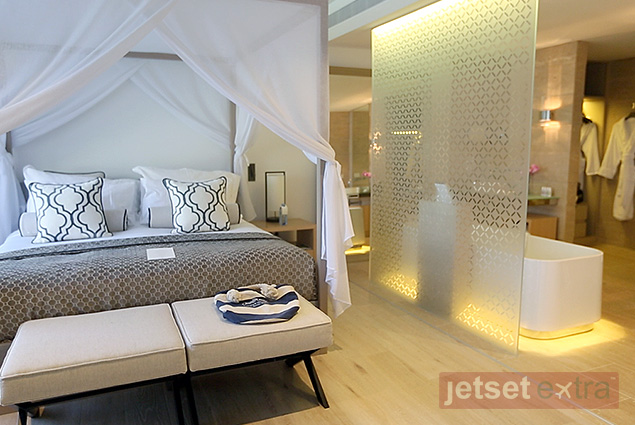 Canopy-draped bed and adjacent bathroom in a Pool Wing suite