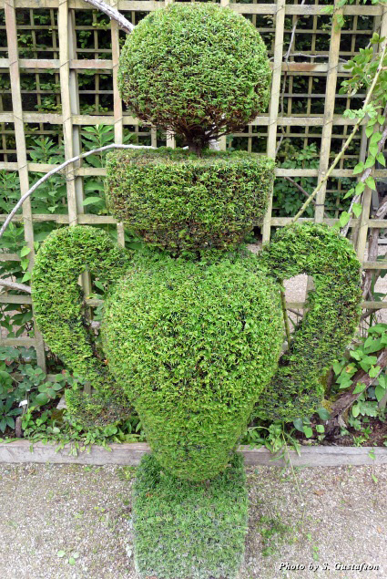 Gardeners use wooden cutouts to precisely trim the bushes into geometrical shapes