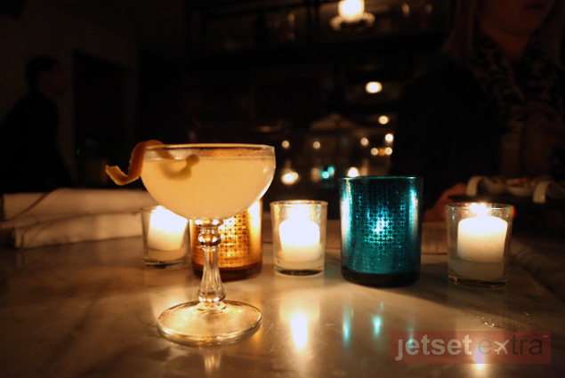 A cocktail lit by candlelight on a table at 1930s House