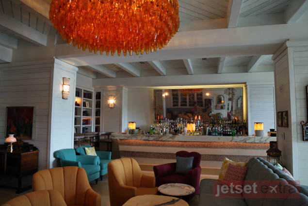 A long mirror along the bar and funky orange chandelier stand out at the cozy Crown Room