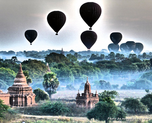 Hot air balloons float over the temples at Bagan during sunrise
