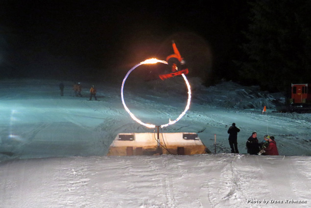 Pro skiers launch through a large hoop in the Fire & Ice Show