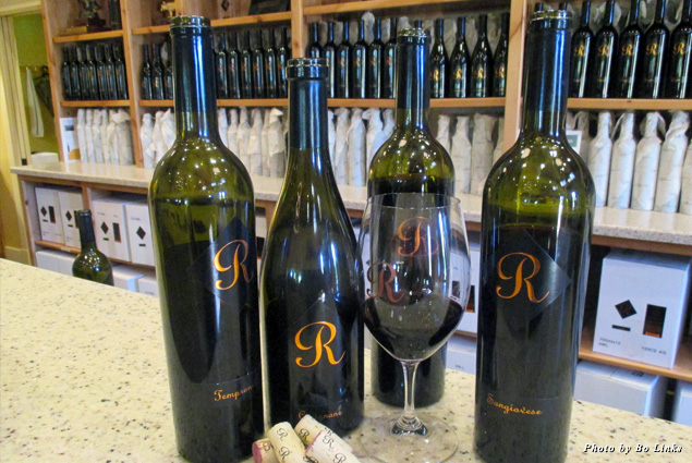 Bottles of Jeff Runquist Wine and a glass of red at the tasting room
