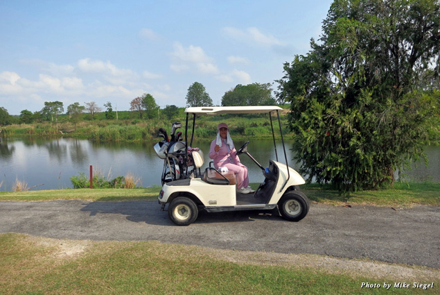 A caddy sits in the golf cart at St. Andrews 2000 Golf Club in Thailand
