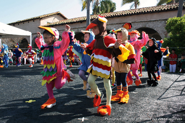 Kids in bird costumes celebrate the Swallows Day Parade at the Mission San Juan Capistrano